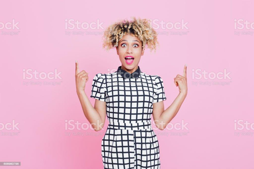 Cute afro american young woman pointing Studio portrait of surprised afro american young woman pointing at copy space. Pink background. 20-24 Years Stock Photo