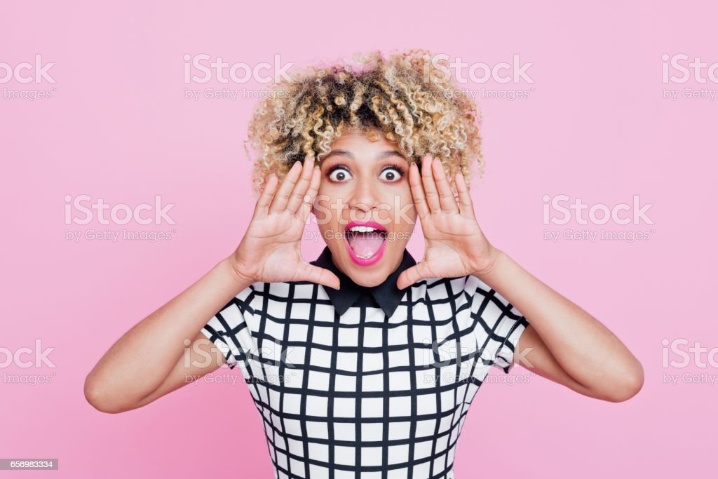 Cute afro american young woman shouting Studio portrait of cute afro american young woman shouting at the camera. Pink background. 20-24 Years Stock Photo