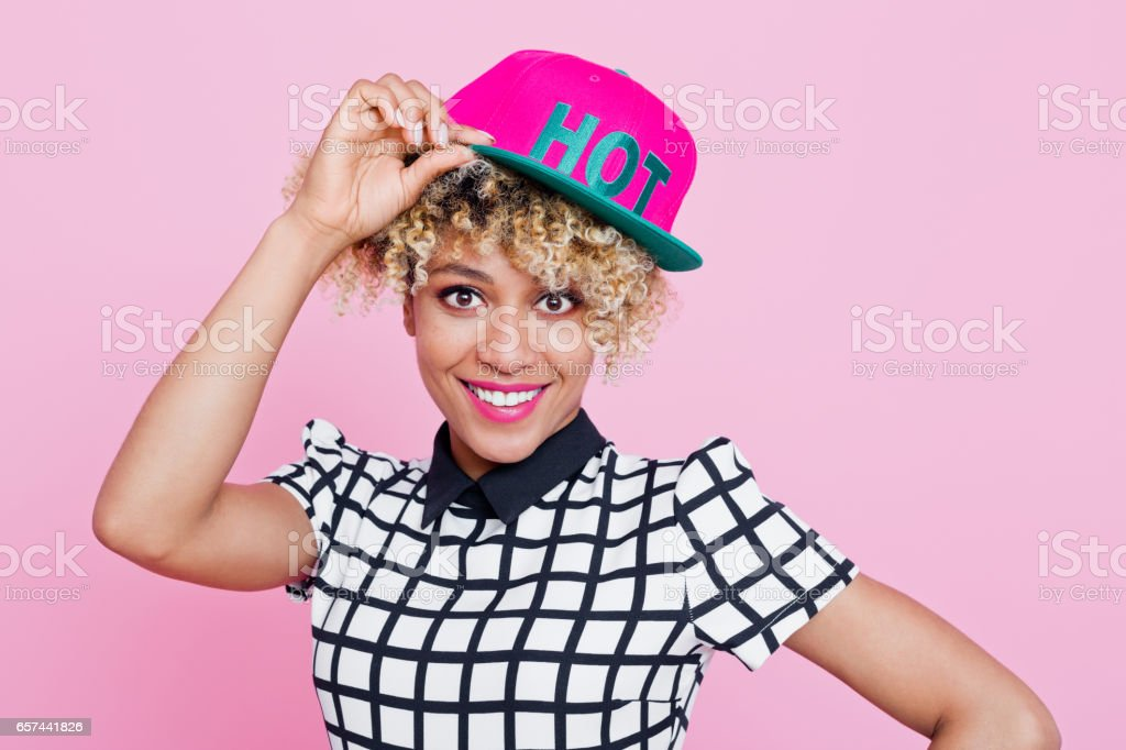 """Cute afro american young woman wearing baseball cap Studio portrait of happy afro american young woman wearing baseball cap with text """"hot"""". Pink background. 20-24 Years Stock Photo"""