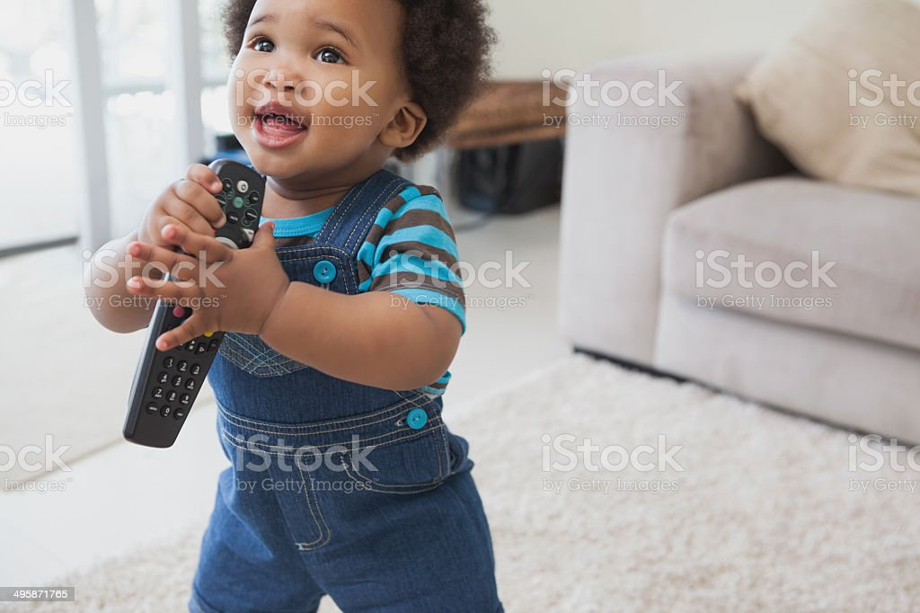 Cute Afro baby holding remote control in living room stock photo