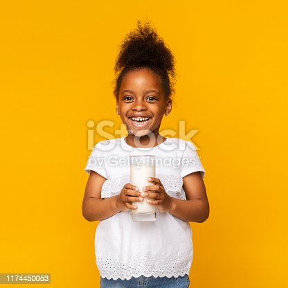 istock Cute afro girl enjoying glass of milk 1174450053