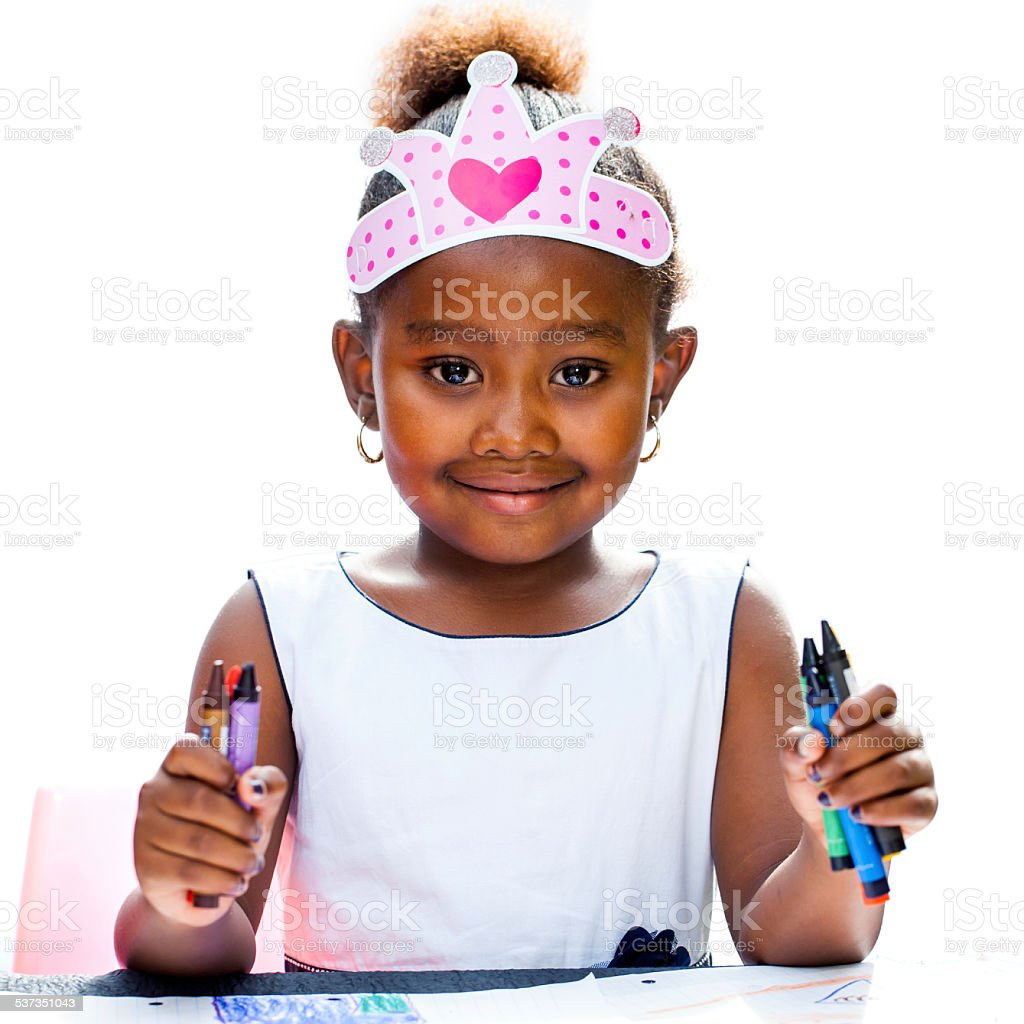 Cute afro girl holding wax crayons. stock photo