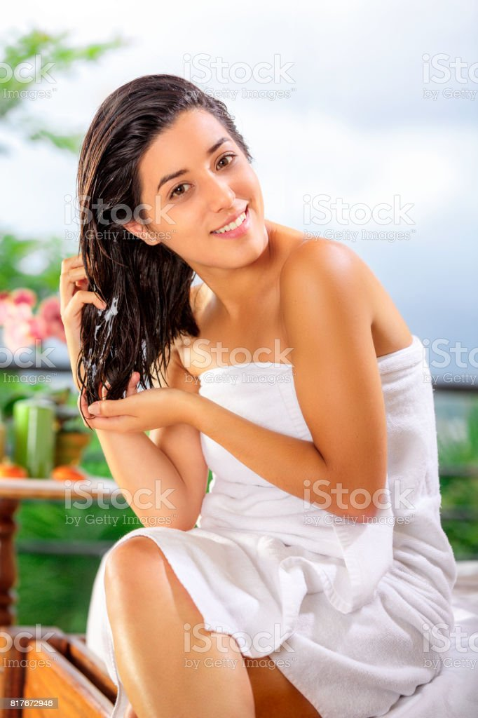 Cute and happy Hispanic young woman doing self hair treatment after bath stock photo