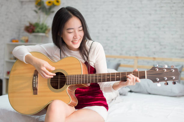 Cute and happy smiling Asian girl playing acoustic guitar in bedroom stock photo