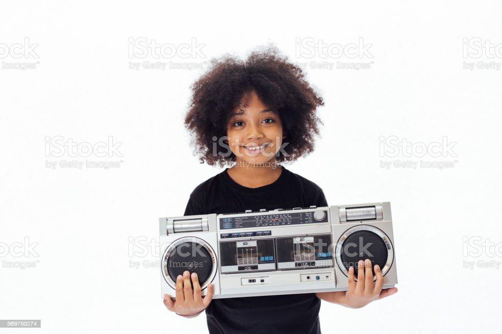 Niedlich und lächelnde Afrikanische amerikanische Kind hält eine musikalische Jukebox isoliert auf weißem Hintergrund – Foto