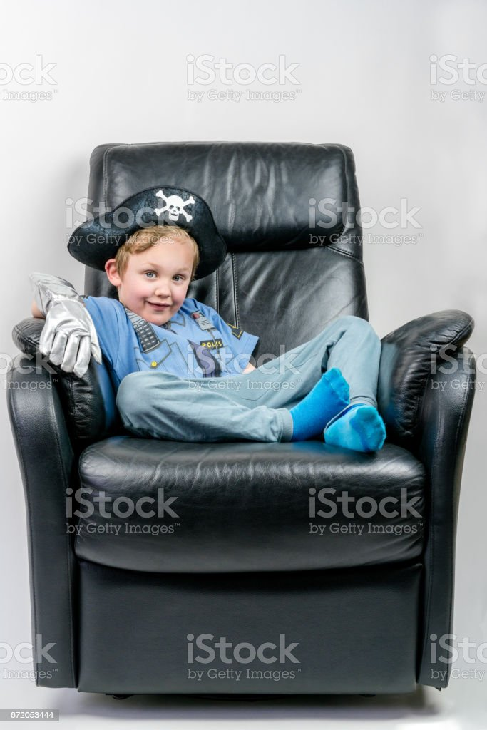 Cute and smiling five year old boy dressed up in a pirate and police officer costume sit and laze in an black leather armchair. stock photo