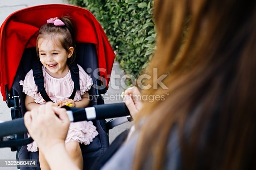 istock Cute and smiling toddler in a baby stroller on a street with her mother 1323560474