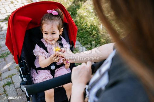istock Cute and smiling toddler in a baby stroller on a street with her mother 1323560537