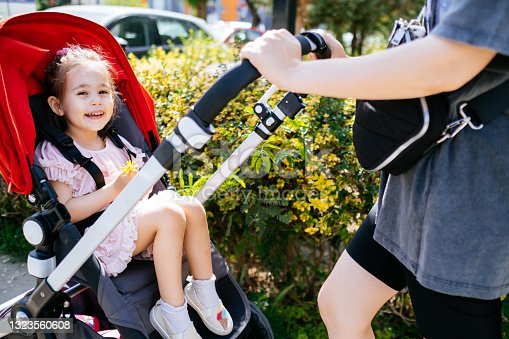 istock Cute and smiling toddler in a baby stroller on a street with her mother 1323560608