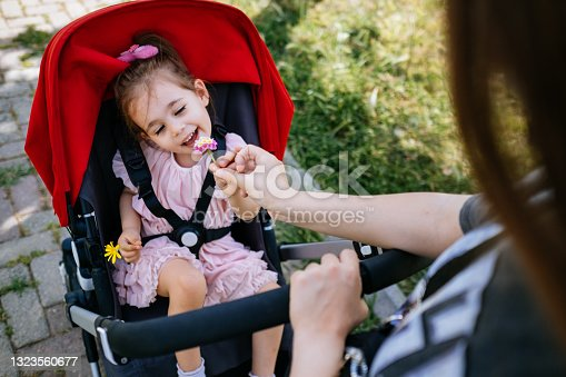 istock Cute and smiling toddler in a baby stroller on a street with her mother 1323560677