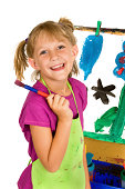 Happy girl in pigtails holds brush infront of her artwork
