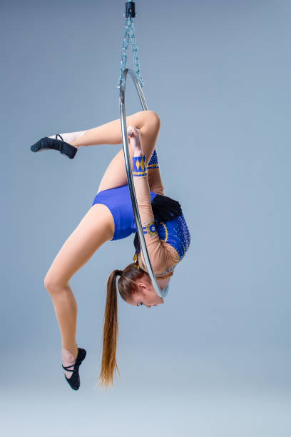 Cute artistic gymnast exercising with hanging hoop stock photo