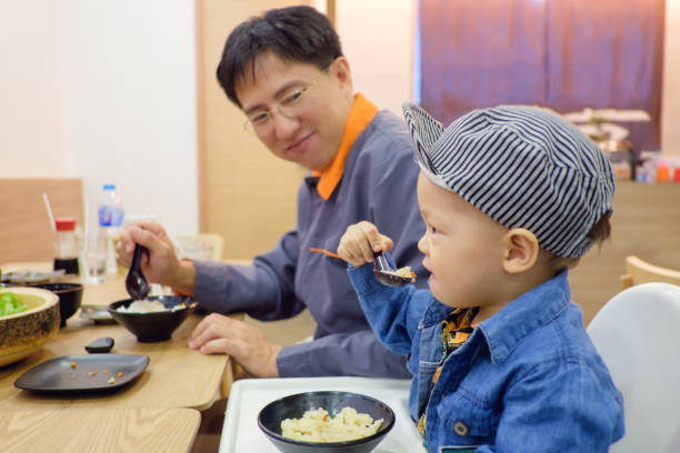 süße asiatische 18 monate kleinkind baby junge kind essen mit gabel & löffel selbst im japanischen restaurant, papa stolz hime - kinderstuhl und tisch stock-fotos und bilder