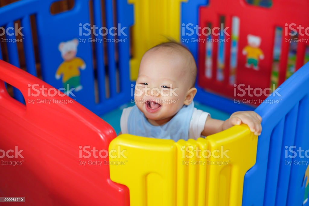 Cute asian 9 months old baby boy playing in colorful plastic playpen, Adorable child having fun indoor, Little smiling kid standing in crib stock photo