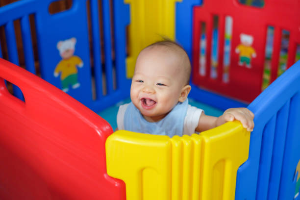 cute asian 9 months old baby boy playing in colorful plastic playpen, adorable child having fun indoor, little smiling kid standing in crib - playpen stock pictures, royalty-free photos & images
