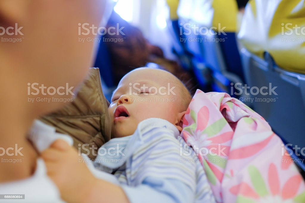 Cute Asian baby boy sleeping on father's laps while traveling in airplane stock photo
