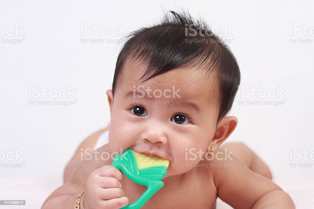 Cute Asian Baby Girl Biting Rubber Toy stock photo