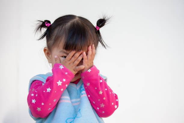 Süße asiatische Babymädchen ihr Gesicht zu schließen und spielen Peekaboo oder Versteckspiel – Foto