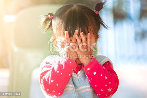 istock Cute asian baby girl closing her face and playing peekaboo or hide and seek 1128821974
