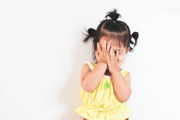 Niedliches asiatisches Mädchen, das ihr Gesicht schließt und Peekaboo spielt oder sich mit Spaß verstecken und suchen – Foto