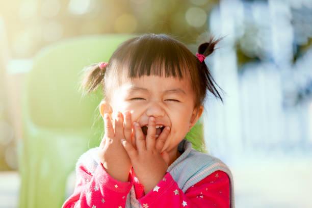 Süße asiatische Babymädchen lachten und spielten Peekaboo oder hide and seek mit Spaß – Foto