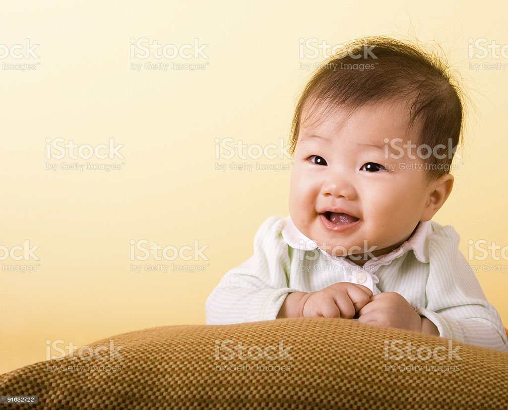 Cute Asian baby resting on a pillow, smiling and happy. Baby teeth...