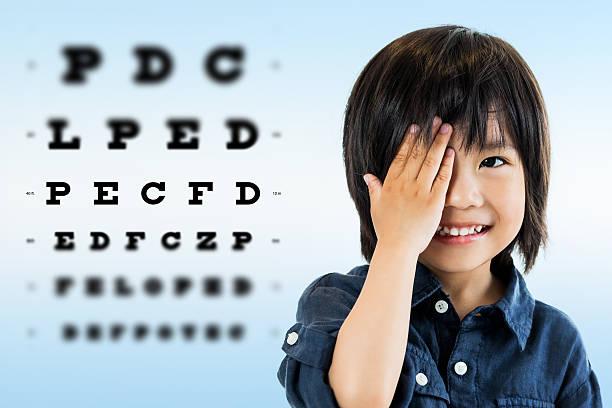 Cute asian boy doing eye test. stock photo