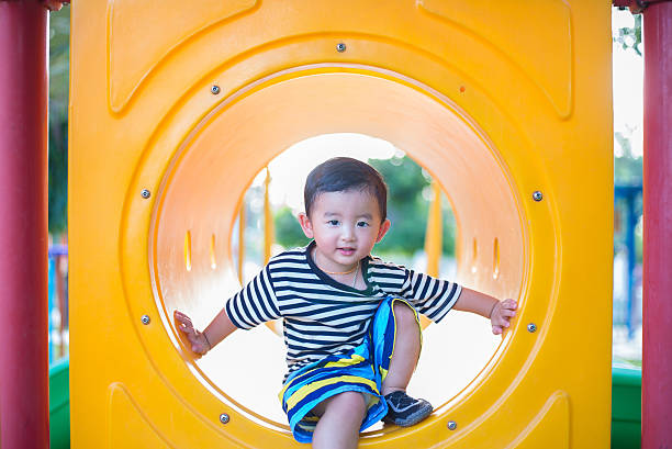 Cute Asian boy playing and smiling in yellow tunnel stok fotoğrafı