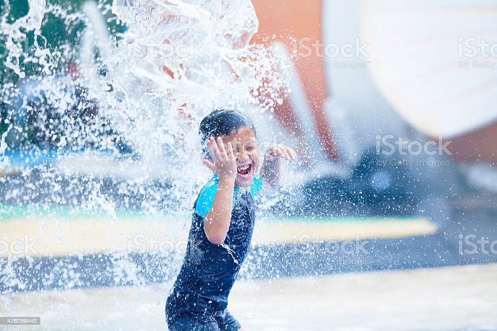 Ładny asian chłopiec bawi się w waterpark – zdjęcie
