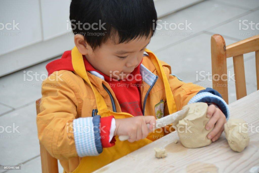 Cute Asian boy playing clay