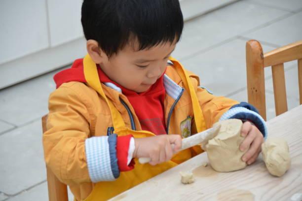 niedlichen asiatischen jungen ton zu spielen - knete spiele stock-fotos und bilder