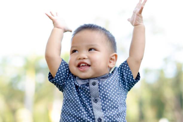 Niedlichen asiatischen Jungen Raise Hände und Lächeln. – Foto