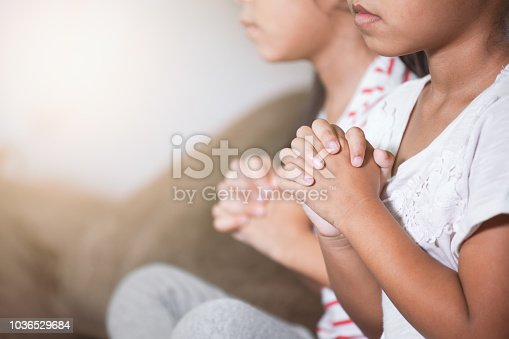 Cute asian child girl and her sister praying with folded her hand in the room together for faith,spirituality and religion concept