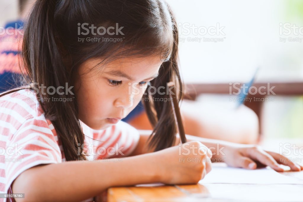 Cute Asian Child Girl Drawing And Painting With Crayon With