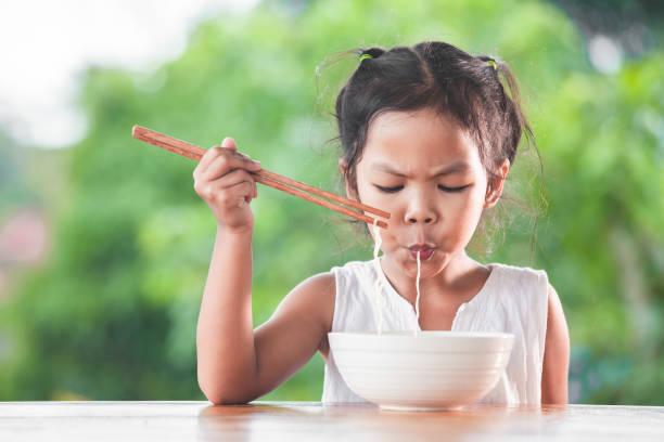 süße asiatische kind mädchen leckere instant-nudeln mit stäbchen zu essen - schnelle suppen stock-fotos und bilder