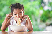 Cute asian child girl eating delicious instant noodles with fork in the nature background