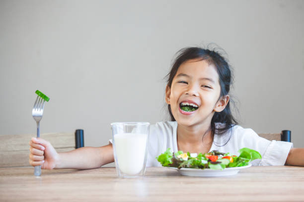 Süße asiatische Kind Mädchen essen gesundes Gemüse und Milch für ihre Mahlzeit – Foto