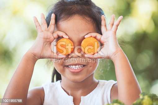 Cute asian child girl having fun to learn about vegetables with happiness