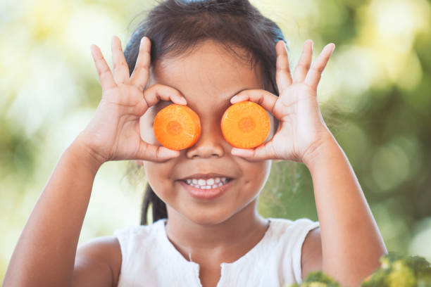 cute asian child girl having fun to learn about vegetables - cenoura imagens e fotografias de stock