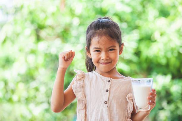 Niedliches asiatisches Mädchen, das Glas Milch hält und starke Geste machen – Foto