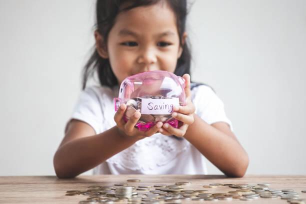 Süße asiatische Kind Mädchen hält Sparschwein und setzen Geld in Sparschwein – Foto