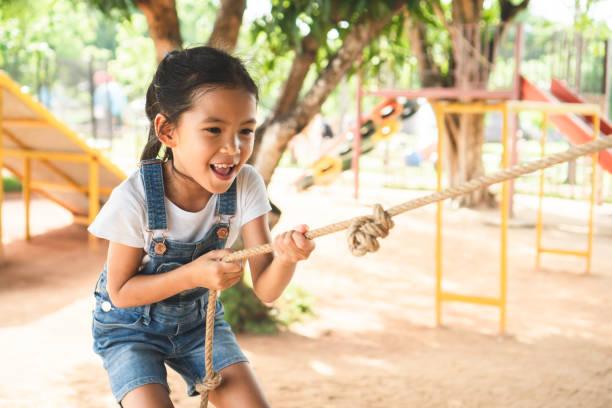 Nette asiatische Kind Mädchen klettert eine Holzwand mit einem Seil auf dem Spielplatz – Foto