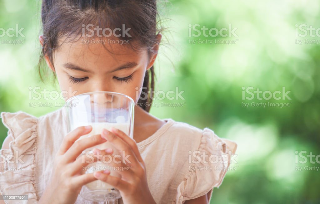 Cute asian child girl is drinking a milk from glass on green nature...