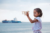 Cute asian child girl playing with toy wooden airplane in the beach with happiness