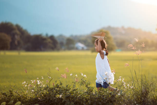 Cute asian child girl running and playing toy paper airplane in the field stock photo