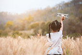 Cute asian child girl running and playing with toy wooden airplane in the barley field at sunset time with fun
