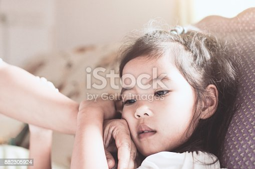istock Cute asian child girl sickness and mother hand touch her face to check temperature 882305924