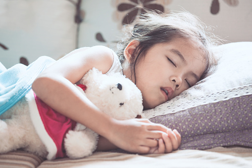 istock Cute asian child girl sleeping and hugging her teddy bear in the bed 851356946