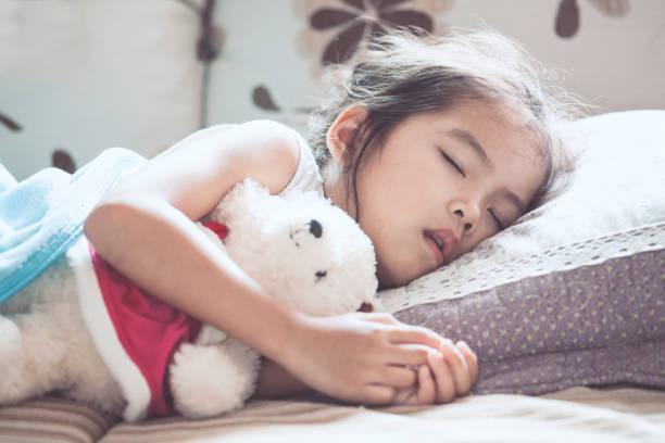 fille mignonne asiatique enfant dormir et étreindre son ours en peluche dans le lit - faire un somme photos et images de collection