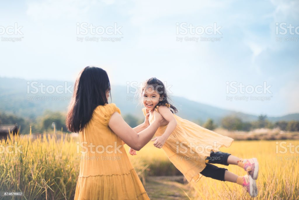 Cute asian child girl smile and fun while mother holding her kid and spinning around stock photo